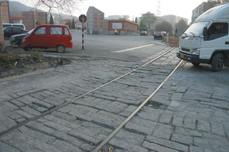 平整的路面突然隆起一排花岗岩,石块夹着两根铁轨,往来车辆途经此处多遇颠簸